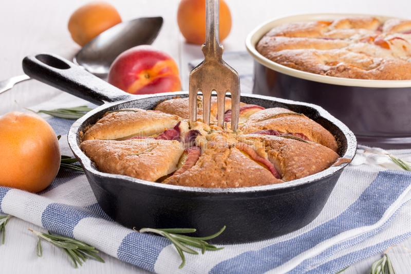 Selbst gemachte Torte mit Pfirsichen, Aprikosen und Rosmarin stockbild