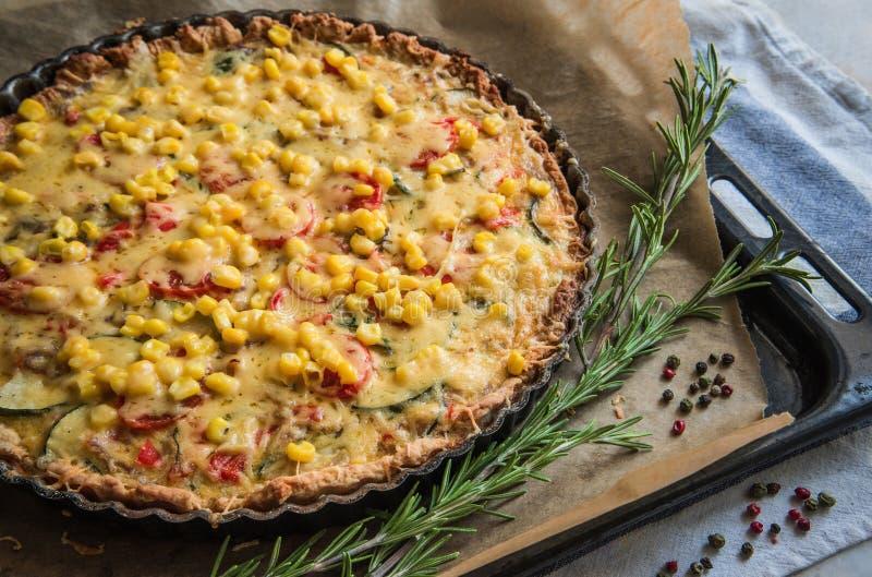 Selbst gemachte Torte mit Zucchini, Tomaten, Käse und Mais auf einem Behälter, mit frischem Rosmarin und farbigem Pfeffer stockfotografie
