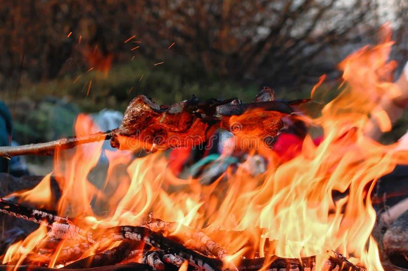 Selbst gemachte Würste und Speck gekocht über einem offenen Feuer in den Bergen in der Natur lizenzfreies stockbild