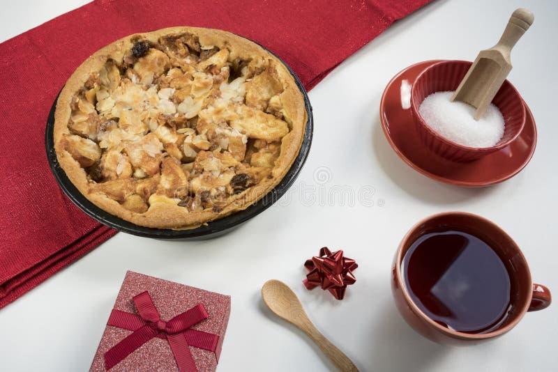 Selbst gemachter Apfelkuchen mit Geschenk, Tasse Tee und Zucker lizenzfreies stockbild