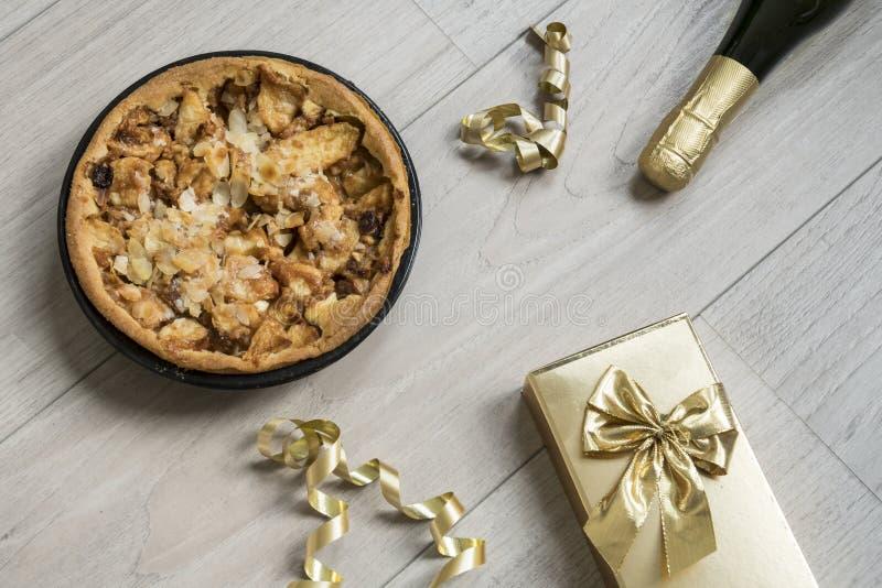 Selbst gemachter Apfelkuchen, mit goldenem Geschenk und Flasche Champagner lizenzfreie stockfotos