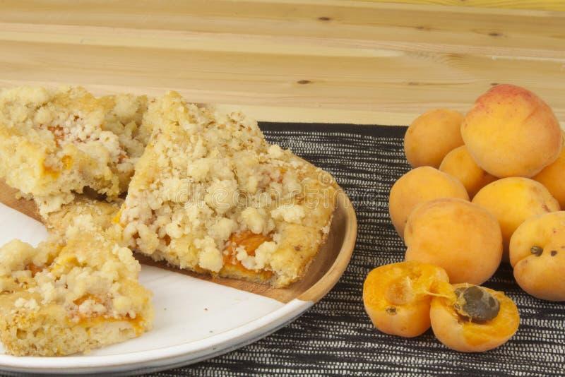 Selbst gemachter Aprikosenkuchen auf einer Platte Frisch ausgewählte Aprikosen auf einem Holztisch stockbilder