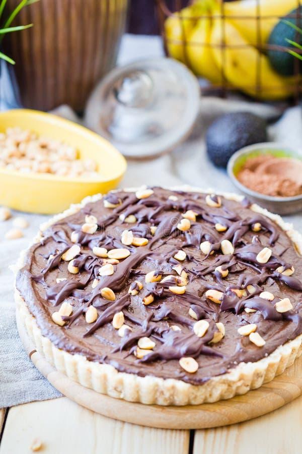 Selbst gemachter Avocado-Schokoladen-Kuchen des strengen Vegetariers mit Erdnüssen und Banane, vertikale Ansicht lizenzfreie stockbilder