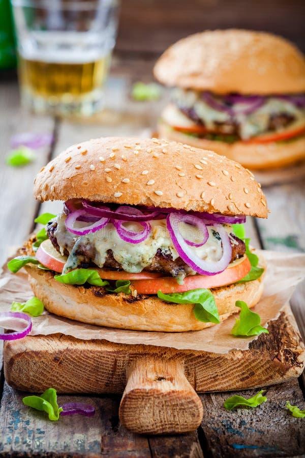 Selbst gemachter Burger mit Rindfleischkotelett, Apfel, Kopfsalat, Zwiebel und Blauschimmelkäse stockfotografie