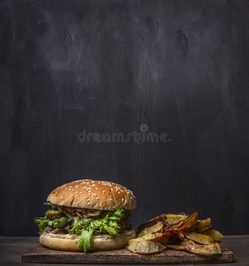 Selbst gemachter Burger mit Thunfisch und gebratenen Kartoffeln mit Dill und Knoblauch auf einer hölzernen rustikalen Hintergrund stockfotos