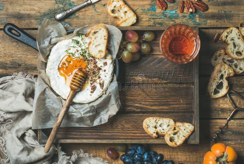 Selbst gemachter Camembert mit Honig, Glas rosafarbenem Wein und Stangenbrot lizenzfreie stockfotos