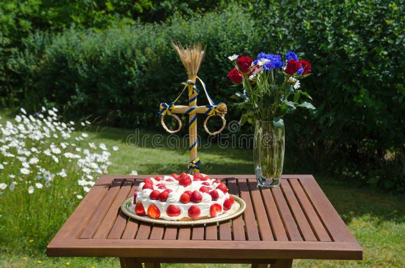 Selbst gemachter Erdbeerkuchen auf verzierter Tabelle im Garten stockbilder