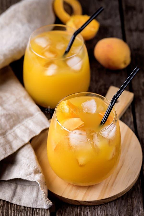 Selbst gemachter frischer geschmackvoller Aprikosen-Saft in den Gläsern auf dem hölzerner Hintergrund-horizontalen gesunde Diät-G stockfotos
