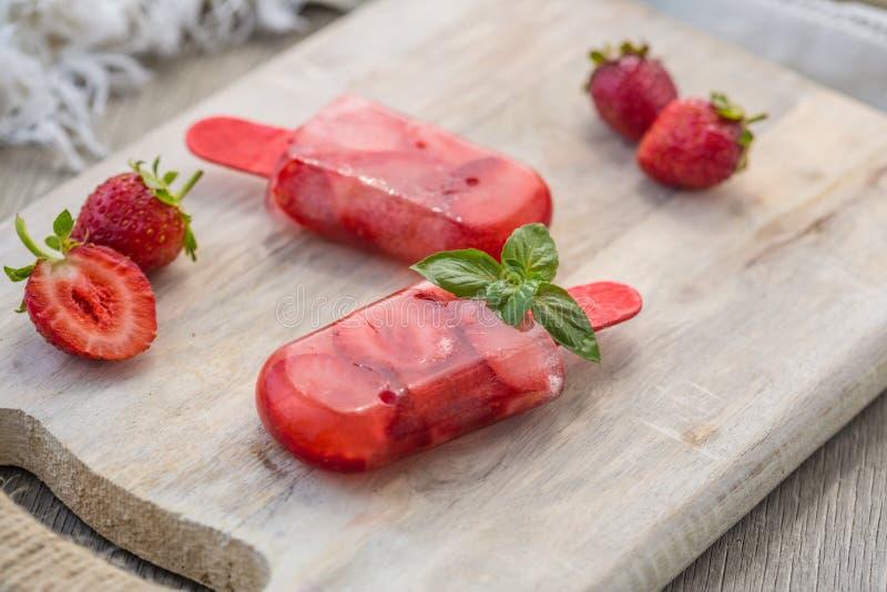 Selbst gemachter Fruchteis am stiel-Stock Köstlicher selbst gemachter Erdbeereis am stiel-Stock auf hellem Hintergrund stockbilder