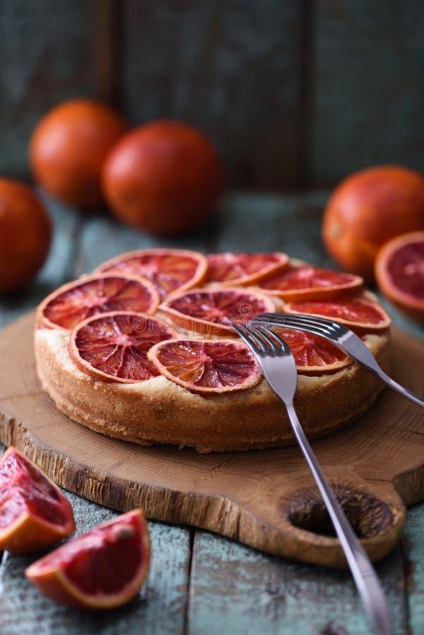 Selbst gemachter Fruchtkuchen Blutorangekuchen diente mit Gabeln und roh lizenzfreies stockbild