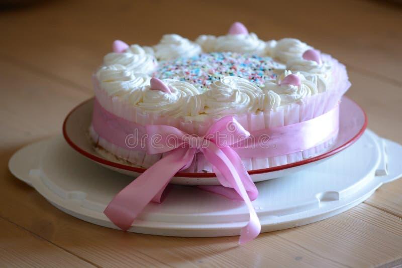 Selbst gemachter Geburtstagskuchen, mit rosa Dragees und Schlagsahne stockbild