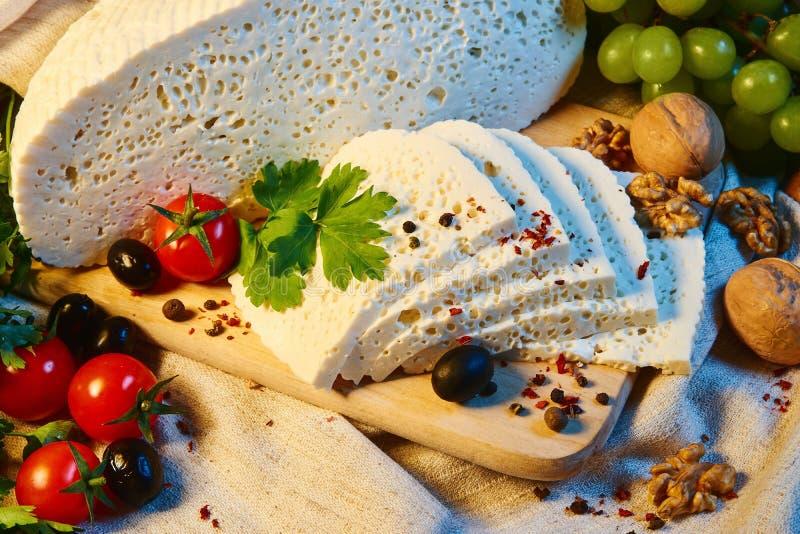 selbst gemachter georgischer Imeretian-Käse auf einem hölzernen Brett, Kirschtomaten, Walnüsse, Trauben, Gewürze lizenzfreie stockbilder