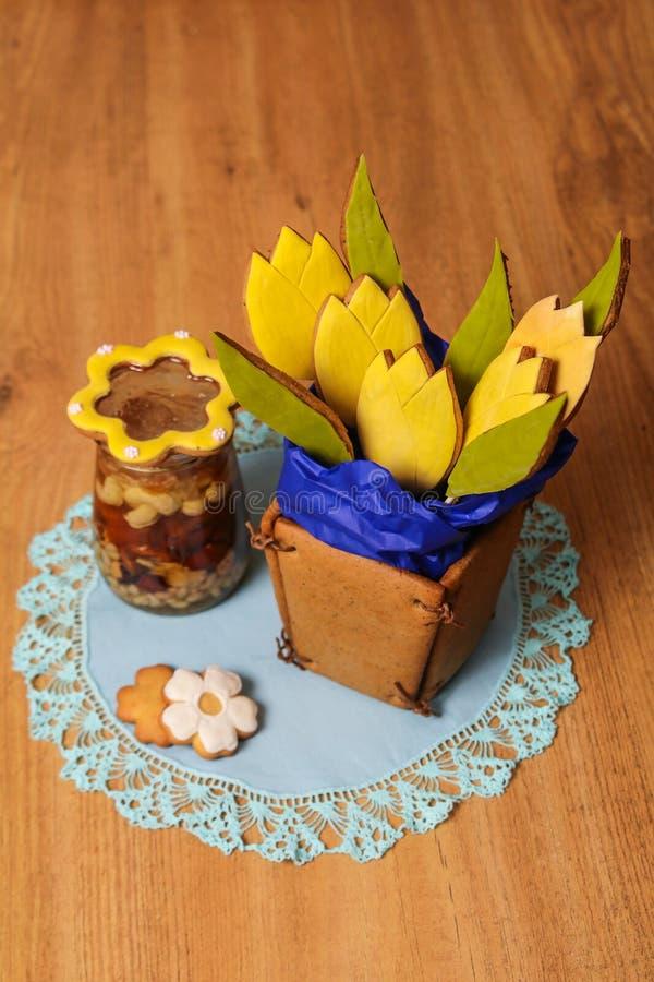 Selbst gemachter Ginger Cookies in Form eines Korbes von Tulpenblumen auf der blauen Serviette nahe einem Glas Honig mit Nüssen a stockfotos