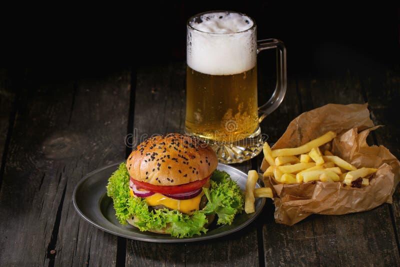 Selbst gemachter Hamburger mit Bier und Kartoffeln lizenzfreie stockfotos