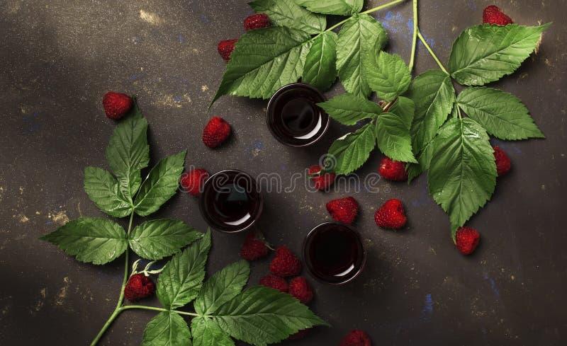 Selbst gemachter Himbeerlikör mit frischen Beeren verzierte grüne Blätter, braunen Tabellenhintergrund, Draufsicht stockbild