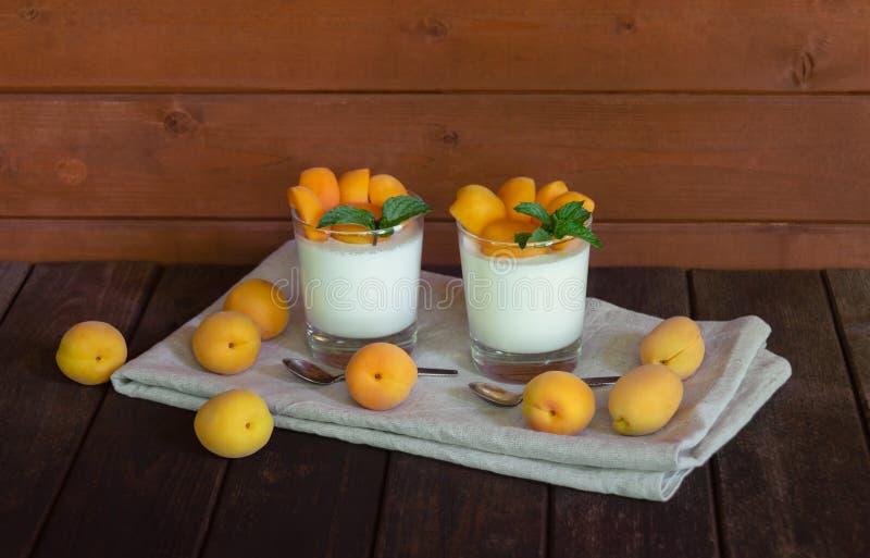 Selbst gemachter italienischer Nachtisch panna Cotta mit den frischen Aprikosen gedient in den kleinen transparenten Gläsern Sele stockfotografie