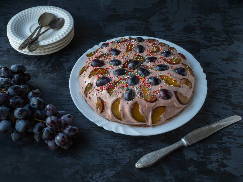 Selbst gemachter Kuchen Kuchen mit Frucht und Beeren auf einer dunklen Tabelle, eine Niederlassung von Trauben und ein Stapel Unt stockbilder