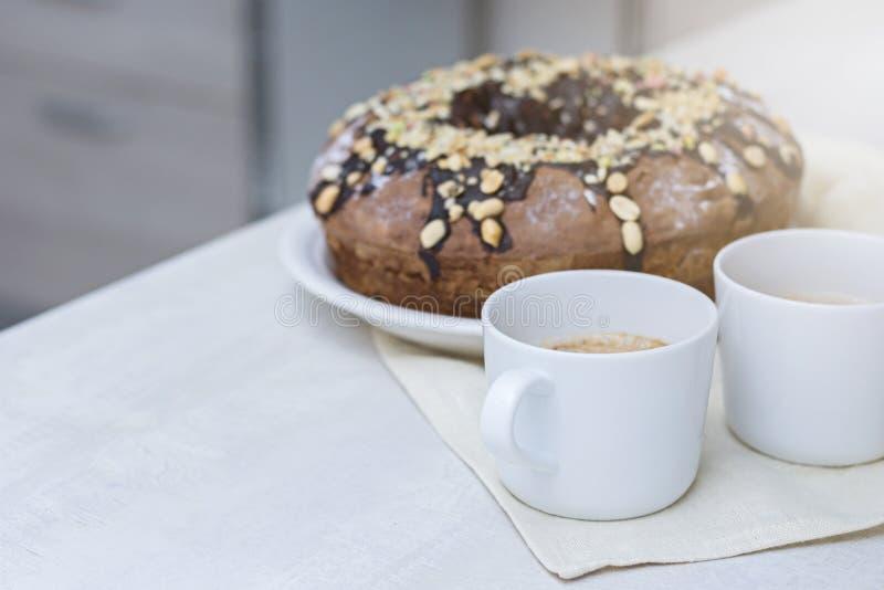 Selbst gemachter Kuchen mit Nüssen und Schokolade und zwei Schalen mit Kaffee auf hölzerner weißer Tabelle stockbilder