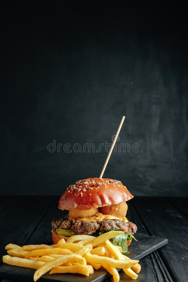 Selbst gemachter saftiger Burger mit Pommes-Frites auf dunklem hölzernem Brett stockbild