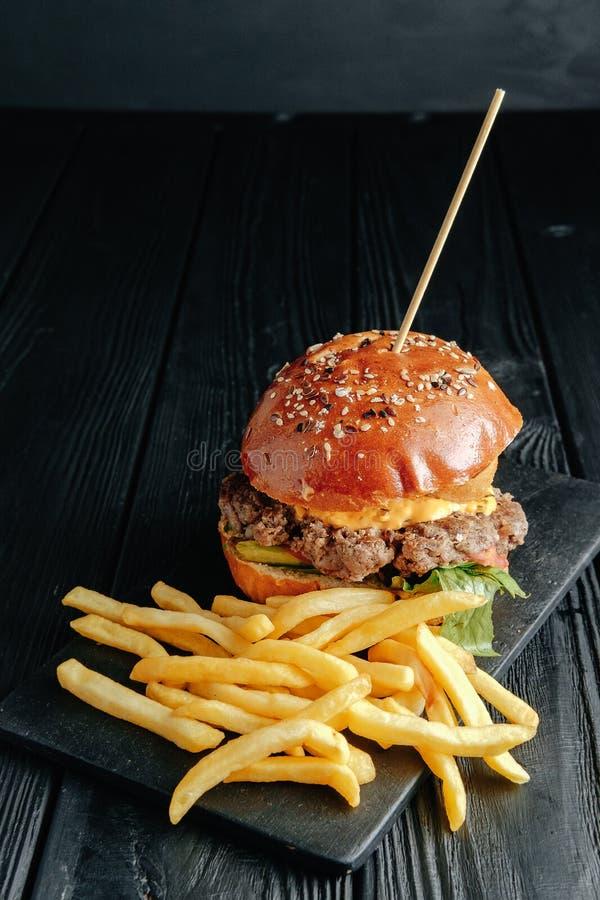 Selbst gemachter saftiger Burger mit Pommes-Frites auf dunklem hölzernem Brett stockfotografie