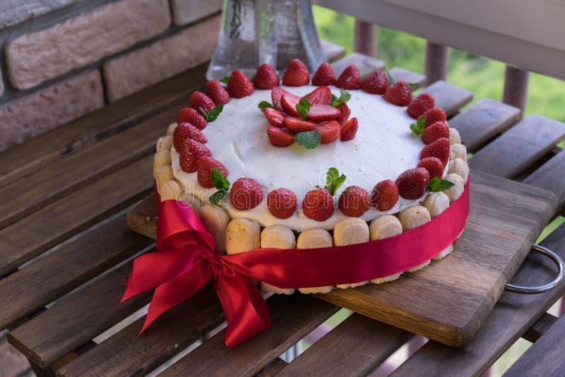 Selbst gemachter Sahnetorten-, frischer, bunter und köstlichernachtisch mit saftigen Erdbeeren, süßer Schlagsahne und Creme stockfoto