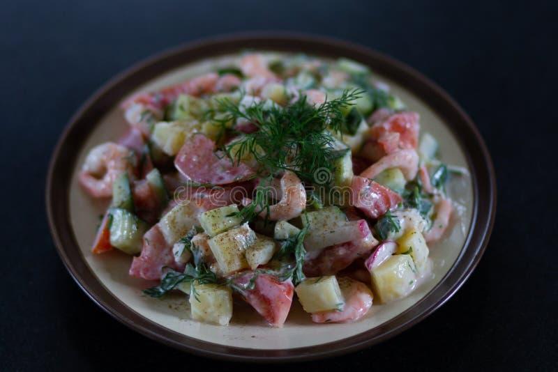 Selbst gemachter Salat mit den Garnelen und Frischgemüse sauced mit dem Jogurt verziert mit Fenchel auf Platte auf schwarzer Tabe stockbilder