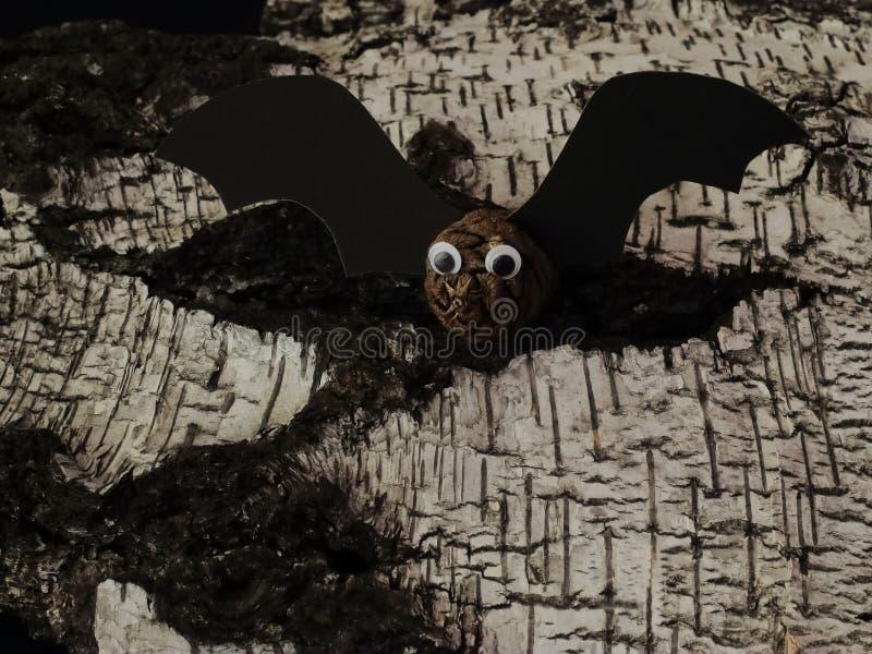 Selbst gemachter Schläger gemacht von den Kiefernkegeln und von der schwarzen Pappe auf alter geschädigter Birkenrinde Symbolisch stockbild