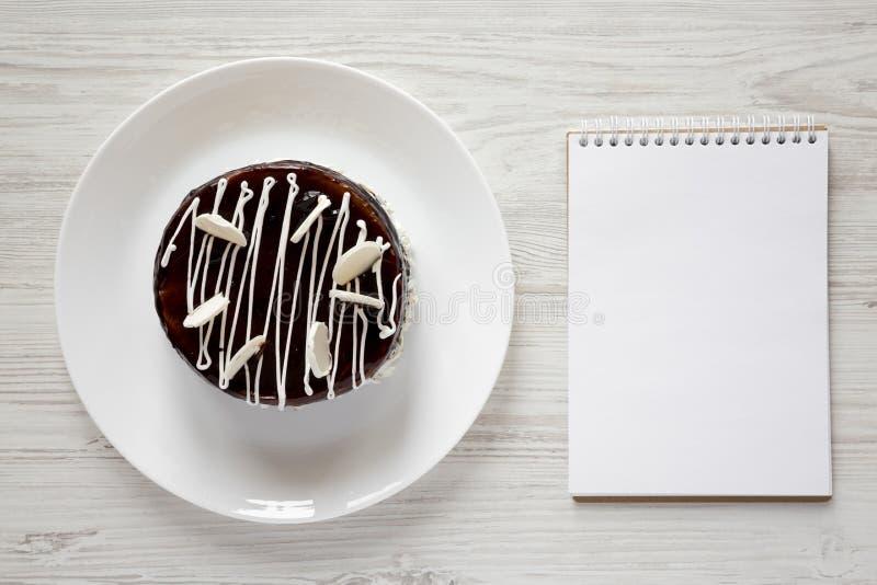 Selbst gemachter Schokoladenkirschkuchen und leerer Notizblock auf weißem hölzernem Hintergrund, Ansicht von oben Flache Lage, Dr lizenzfreie stockbilder