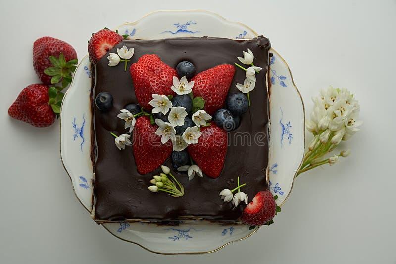 Selbst gemachter Schokoladenkuchen verziert mit Erdbeeren und essbaren Blumen stockbilder