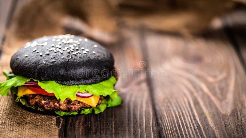 Selbst gemachter schwarzer Burger mit Käse Cheeseburger mit schwarzem Brötchen auf dunklem hölzernem Hintergrund stockfotografie