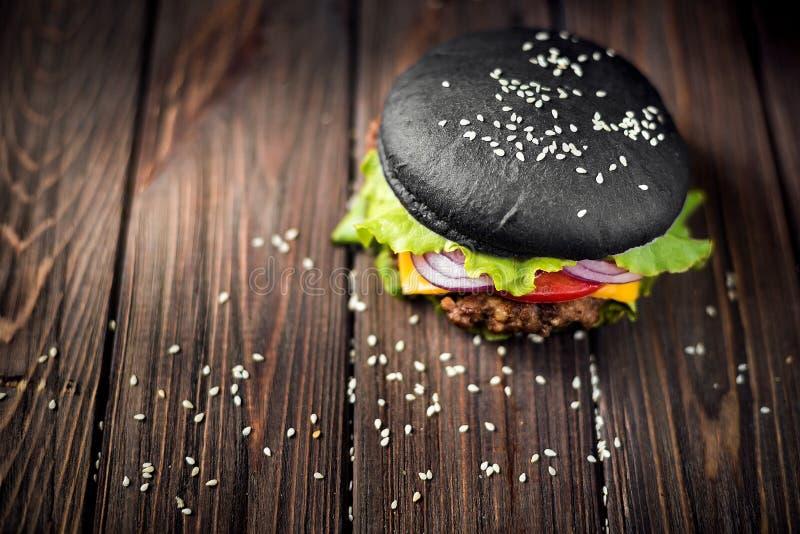 Selbst gemachter schwarzer Burger mit Käse Cheeseburger mit schwarzem Brötchen O stockfoto