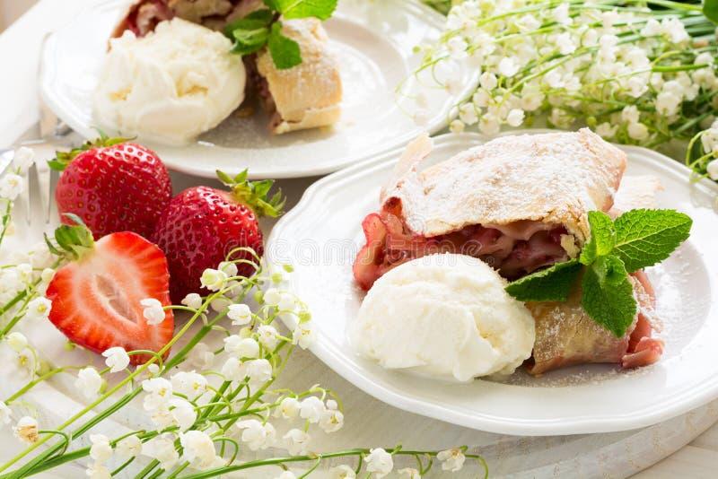 Selbst gemachter Strudel mit Erdbeeren verzierte Eiscreme und tadellose Blätter stockbilder