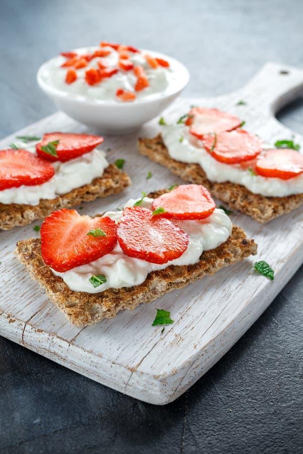 Selbst gemachter Toast des knusprigen Brotes mit Hüttenkäse und Erdbeere auf weißem hölzernem Brett stockfoto