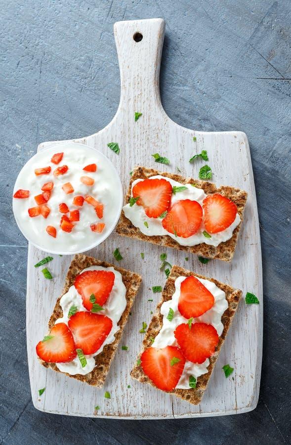 Selbst gemachter Toast des knusprigen Brotes mit Hüttenkäse und Erdbeere auf weißem hölzernem Brett stockfotos