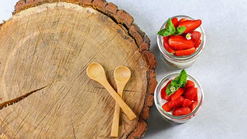 Selbst gemachter, vorzüglicher Nachtisch Tiramisu in den Gläsern verziert mit Erdbeere, Minze, auf einem hölzernen Stumpf Authent lizenzfreie stockfotografie