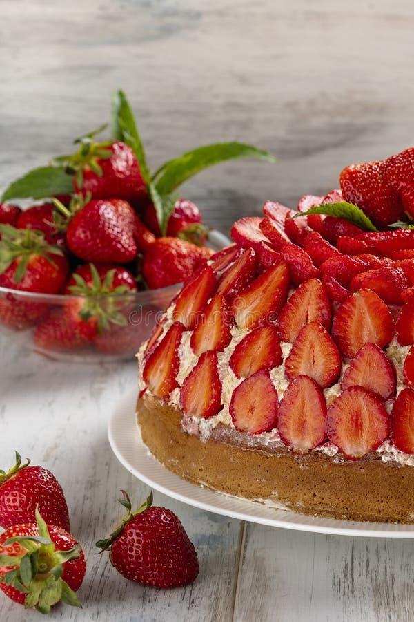 Selbst gemachtes B?ckereikonzept Erdbeerkuchen mit Vanillecreme verzierte mit frischen Erdbeeren und Minze auf einem h?lzernen Hi lizenzfreies stockfoto