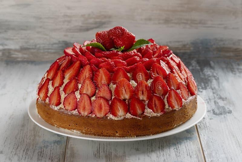 Selbst gemachtes B?ckereikonzept Erdbeerkuchen mit Vanillecreme verzierte mit frischen Erdbeeren und Minze auf einem h?lzernen Hi lizenzfreies stockbild