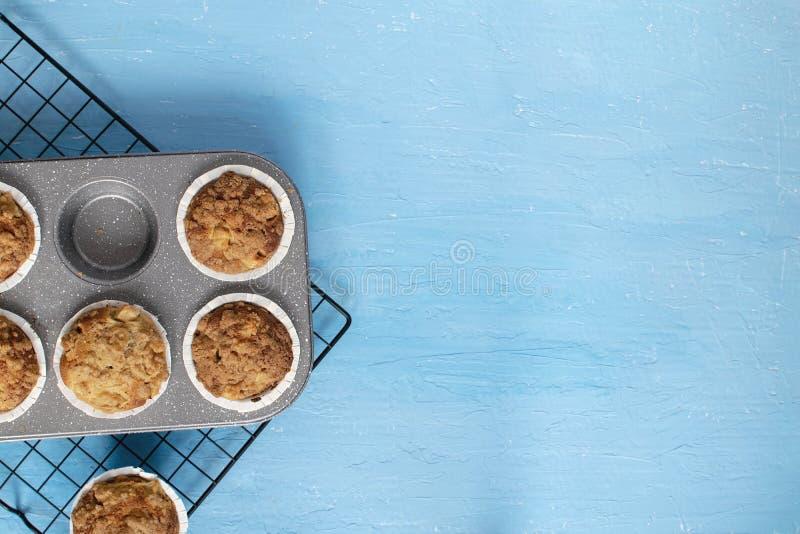 Selbst gemachtes backendes Konzept - frische gebackene Muffins auf abkühlendem Gestell, minimales Bild, heller blauer Hintergrund stockbilder