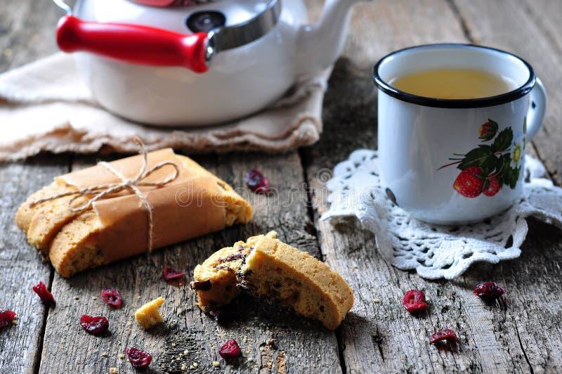 Selbst gemachtes biscotti mit getrockneten Moosbeeren und Kalk, mit einer Schale des Kessels des grünen Tees auf dem Holztisch lizenzfreie stockfotografie