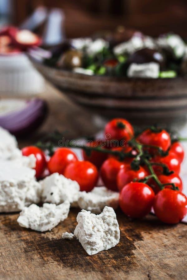 Selbst gemachtes Feta mit Kirschtomaten und griechischem Salathintergrund auf Holztisch stockbild