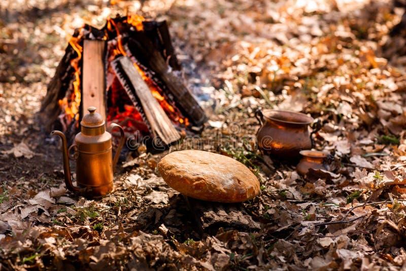 Selbst gemachtes frisches Brot auf dem Hintergrund des Feuers im Herbstwald lizenzfreie stockbilder