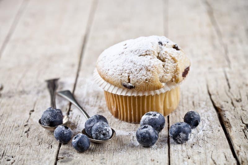Selbst gemachtes frisches Muffin mit Zuckerpulver, Weinleselöffeln und Blaubeeren auf auf rustikalem Holztisch lizenzfreies stockbild