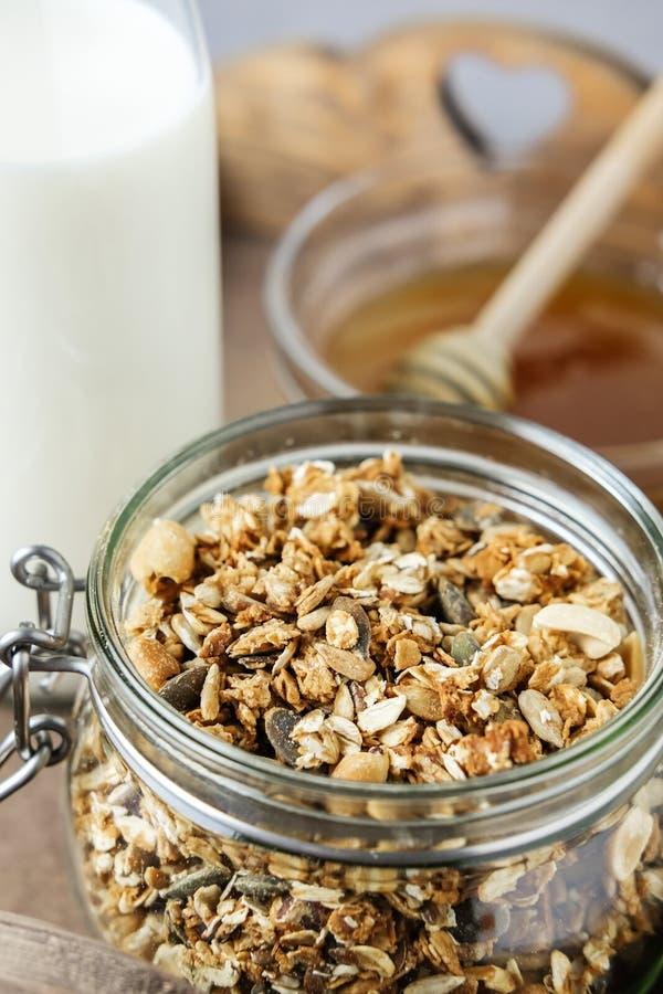 Selbst gemachtes Granola in einem Glasgefäß auf einem hölzernen Behälter und einer Flasche Milch und Honig Nützliches Frühstück lizenzfreie stockfotografie