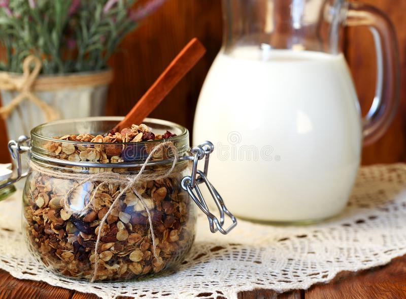 Selbst gemachtes Granola mit Nüssen, Moosbeeren und getrocknete Aprikosen und ein Krug Milch Selektiver Fokus, Kopienraum stockfotografie