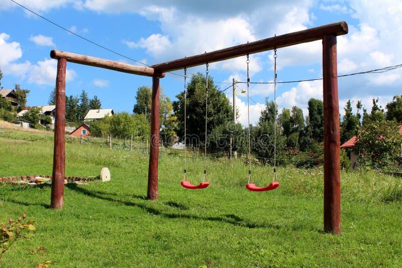 Selbst gemachtes hölzernes Spielplatzschwingen im Freien mit starkem Holzrahmen im Hinterhof umgeben mit ungeschnittenem Gras und lizenzfreie stockfotos