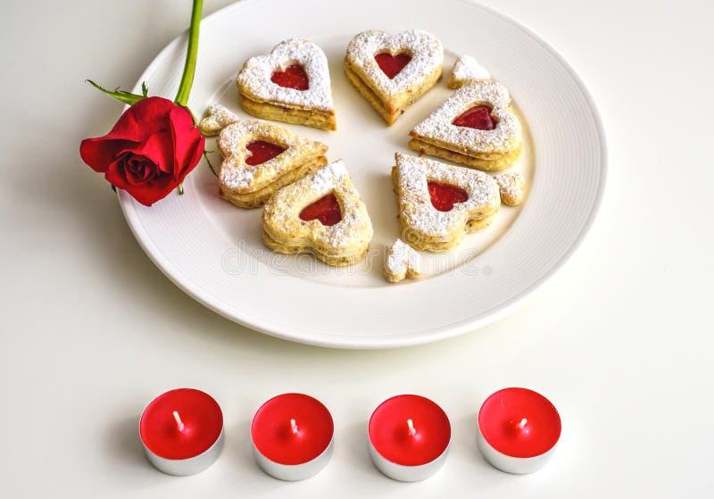Selbst gemachtes Herz formte Mandel Linzer-Plätzchen auf weißer Platte Jahrestag ffor rote Rosen der romantischen Einrichtung und lizenzfreie stockfotografie