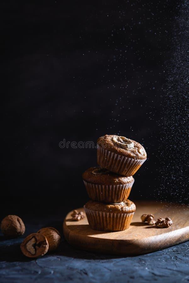 Selbst gemachtes köstliches Muffin besprüht mit Puderzucker auf dunkler Hintergrundnahaufnahme Schalenkuchen mit Banane und Walnu lizenzfreie stockbilder