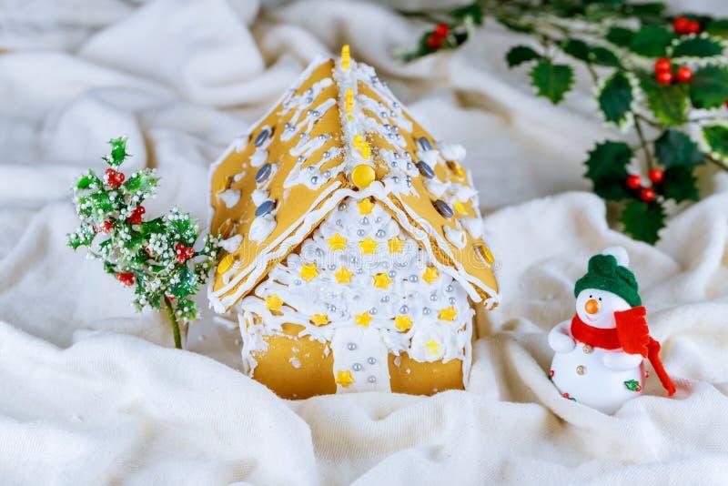 Selbst gemachtes Lebkuchenhaus mit Weihnachtsdekorationen, künstliche Schneefälle stockfotografie