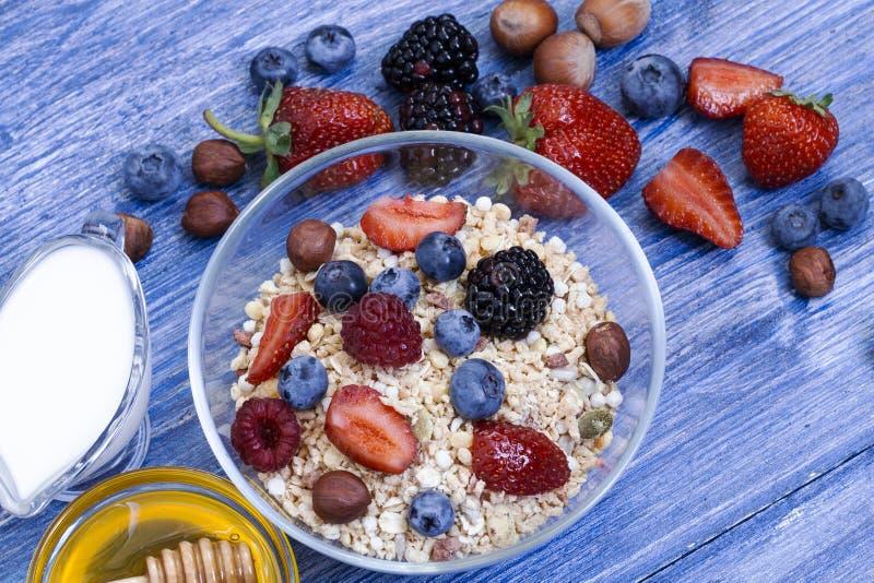 Selbst gemachtes muesli oder Granola in der Schüssel mit Milch, Honig, Beeren und Nüssen Healty Frühstücks-Draufsicht Köstliches  stockfotografie