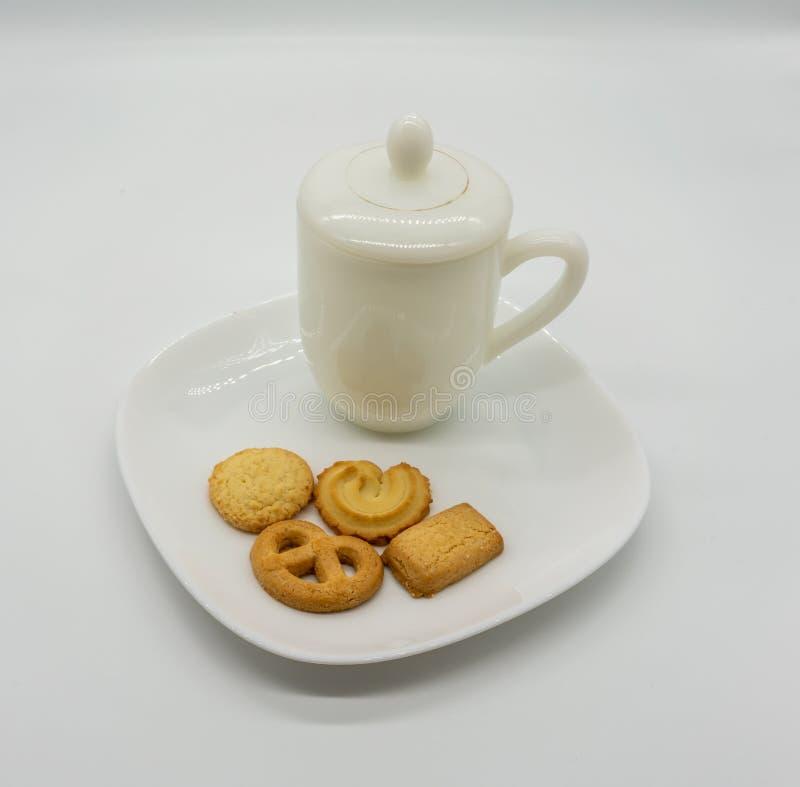 Selbst gemachtes Plätzchen und Tee auf dem keramischen Teller lokalisiert auf Weiß stockfotos